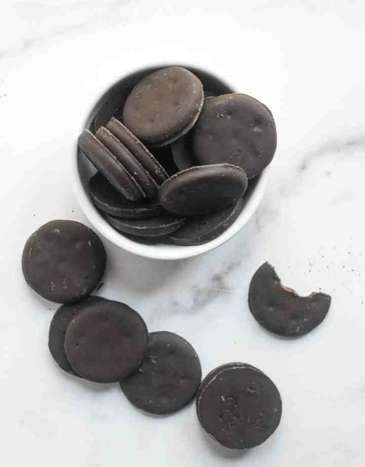 thin mint cookies in a bowl with several thin mints around bowl, including one half bitten.