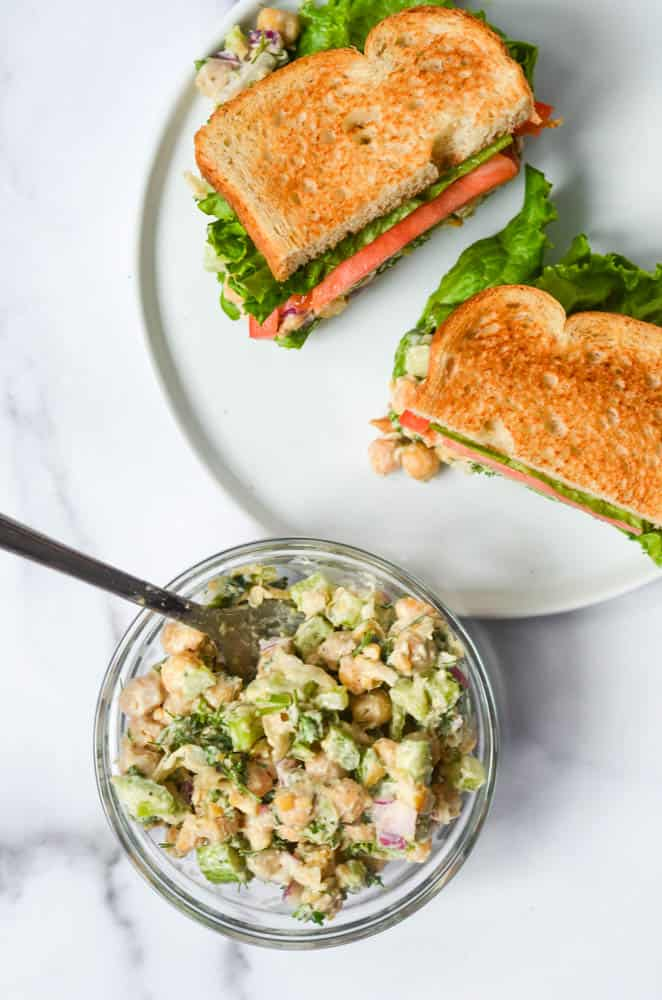 "bowl of chickpea ""chicken"" salad with two halves of sandwiches on a white plate"