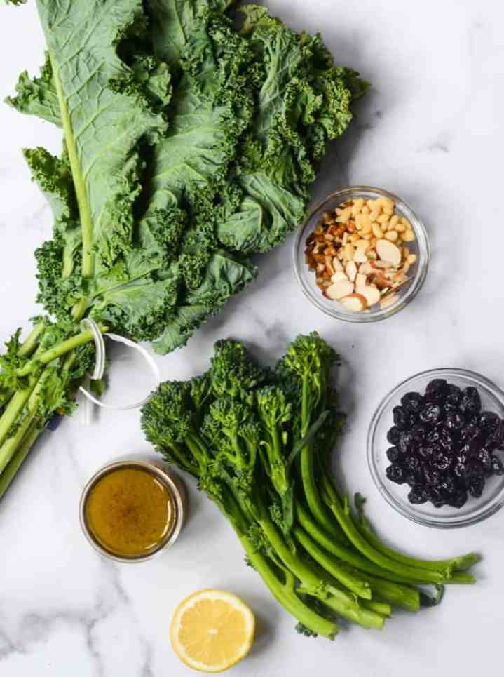 flat lay of all ingredients needed to make kale salad: kale, broccolini, nuts, sour cherries, lemon, and maple vinaigrette.