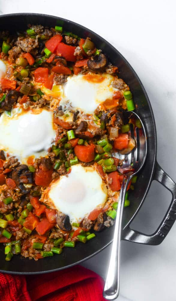shakshuka in cast iron skillet with spoon under ingredients.