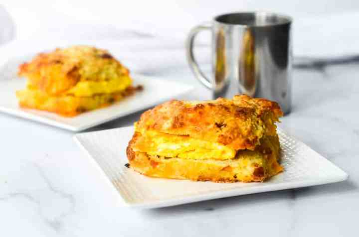 side photo of egg in between bacon and cheddar biscuit with coffee cup and another egg sandwich in the background.