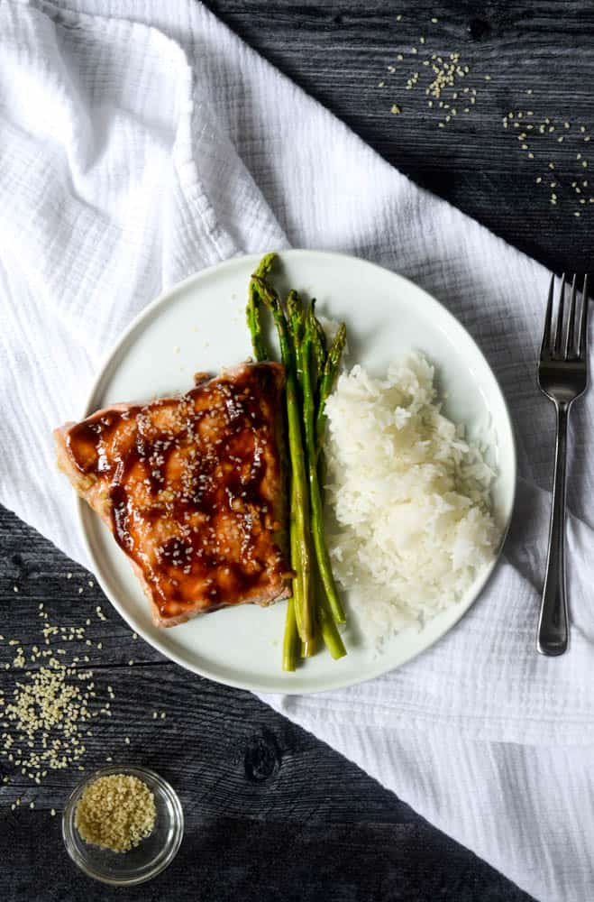 aerial view of baked teriyaki salmon, asparagus, and rice on white plate on black background with toasted sesame seeds sprinkled on background