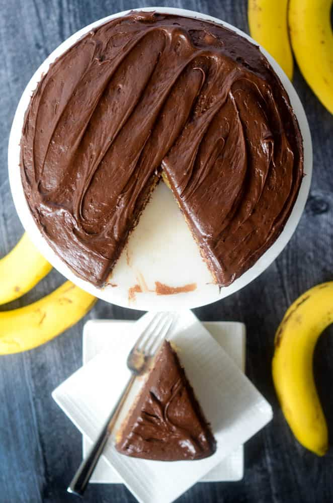 one slice on plate in background with rest of cake in the focus. bananas in background
