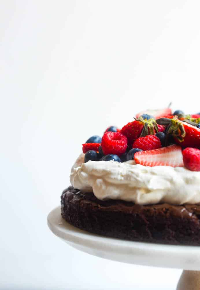 side view of brownie pizza cake with mixed berries on top of fluffy whipped cream on top of brownie