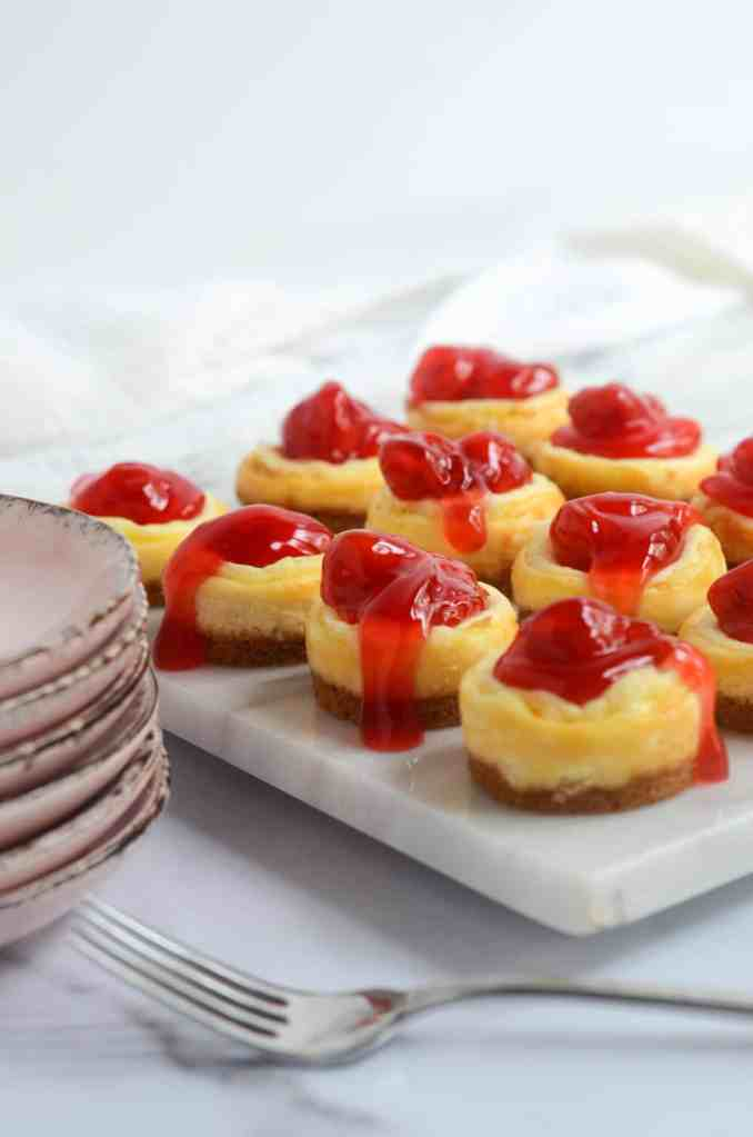 side show of cheesecake bites with stack of pink plates and fork in the background