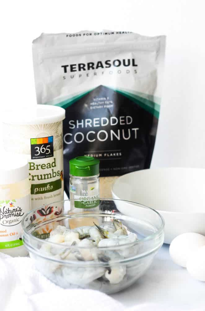 bag of coconut, bread crumbs, garlic powder, coconut oil, and bowl of shrimp.