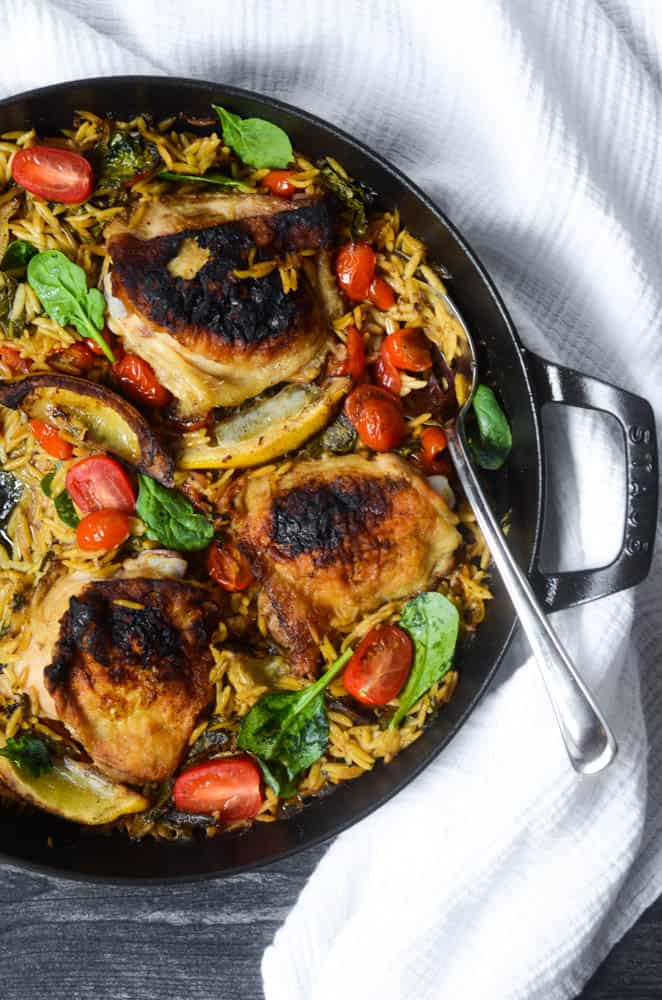 aerial view of black skillet with lemon chicken orzo with spoon in it.