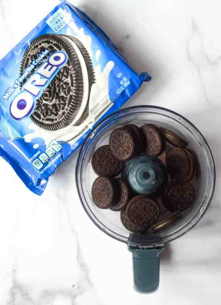 food processor bowl with Oreos in it next to package of Oreos.