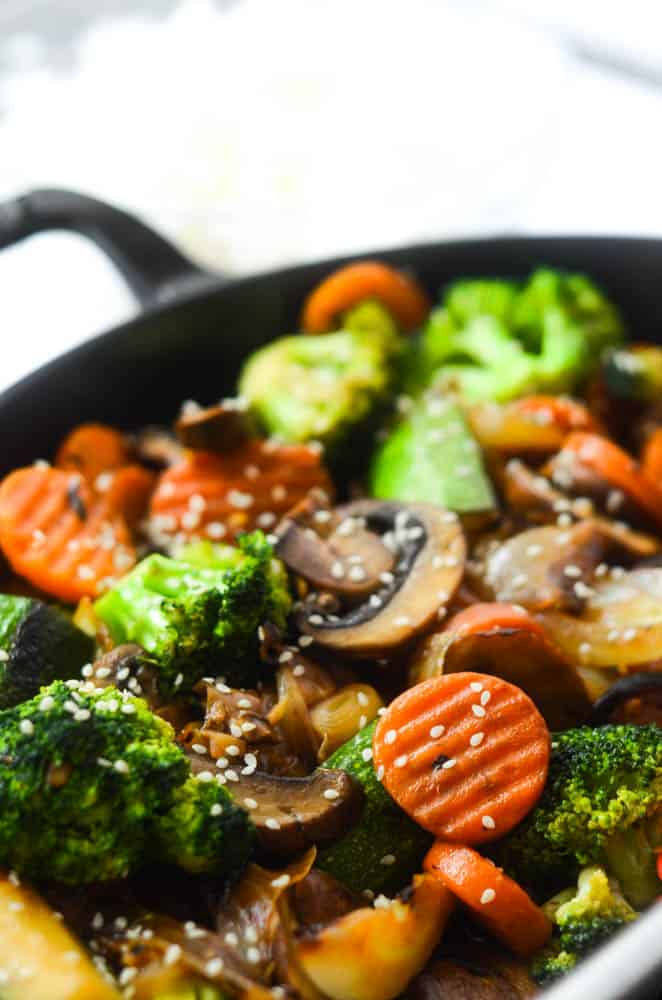up close picture of vegetables sautéing in pan topped with sesame seeds