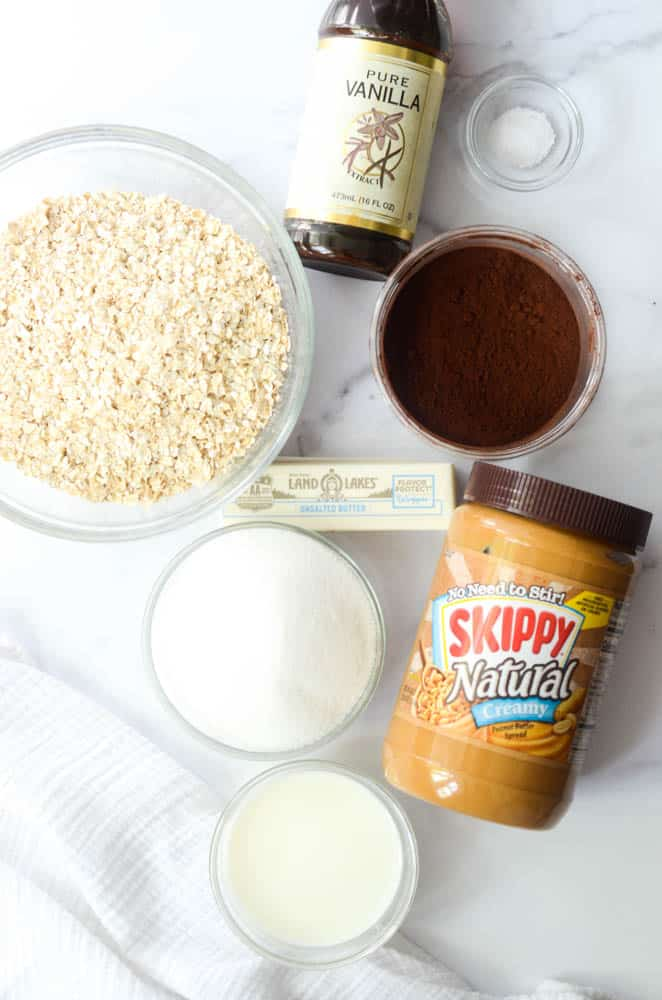 flat lay picture of ingredients needed to make no bake chocolate oatmeal cookies  on granite background - peanut butter, sugar, butter, milk, cocoa powder, vanilla extract and oats.