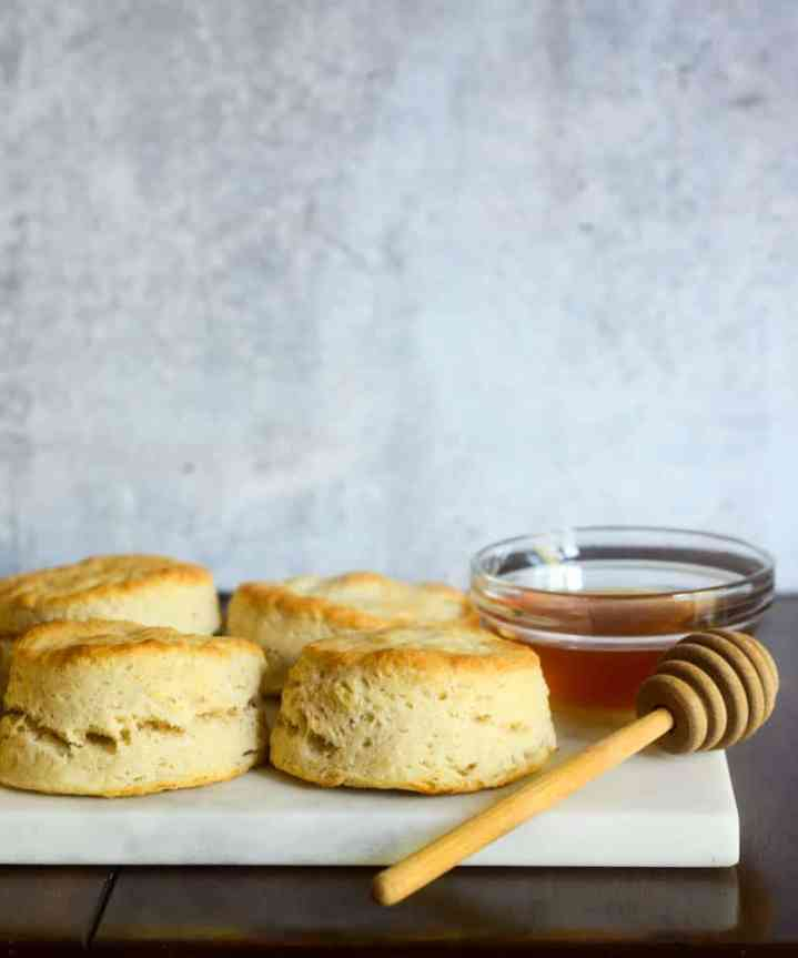 biscuits on marble slab with bowl of honey and honey comb.