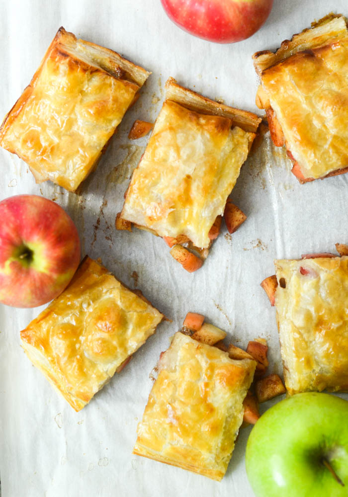 flat lay of cut apple slab pie with apples scattered.