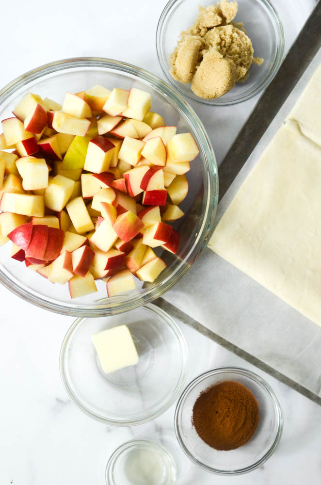 aerial view of ingredients needed: cinnamon, sugar, apples, brown sugar, puff pastry, lemon juice all in bowls.