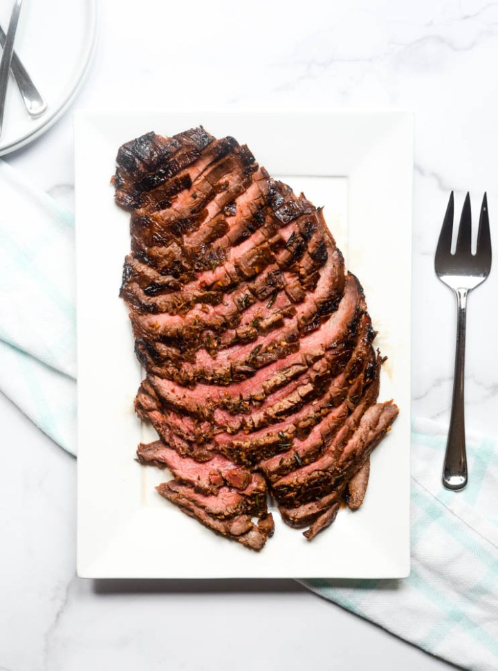 aerial view of white platter with flank steak, plates in corner and serving fork next to platter.
