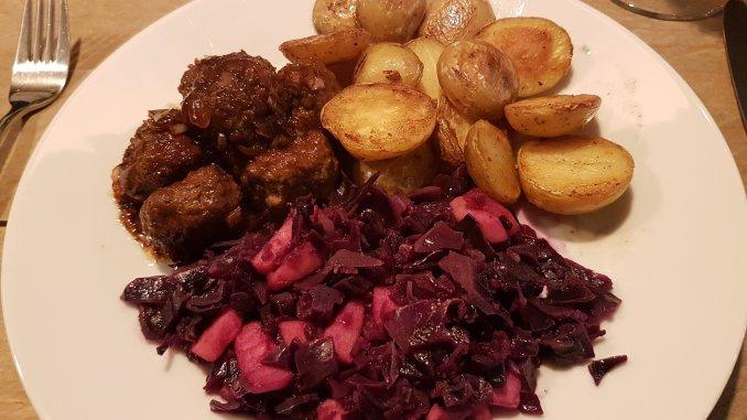 Rode kool uit de stoomoven op bord met gehaktballetjes en gebakken aardappels