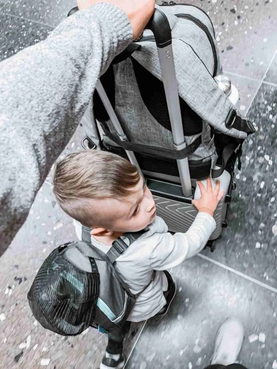 Little boy pushing carry-on suitcase through airport for family minimalist travel