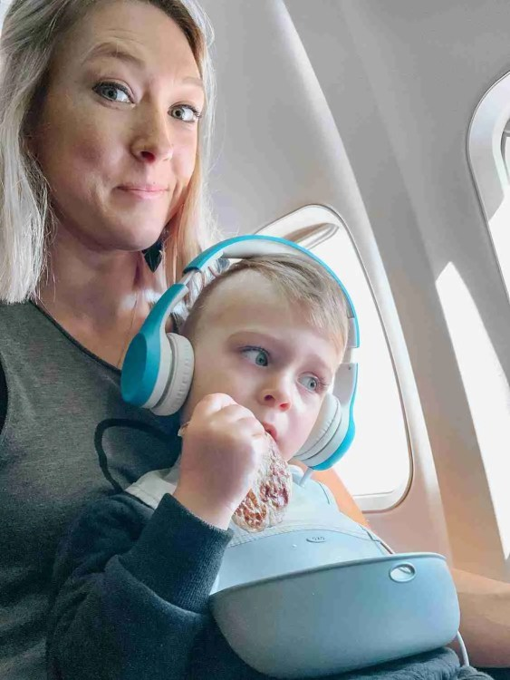 Little boy sitting on mom's lap on airplane with bib and snacks and headphones on