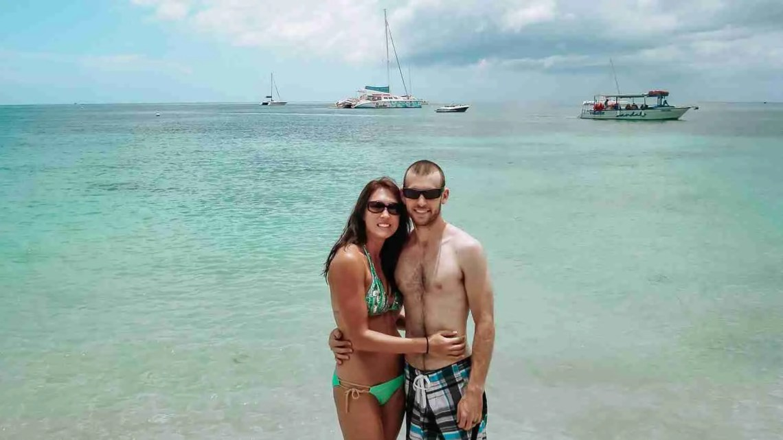 Travel as a couple on a Jamaican beach with teal water