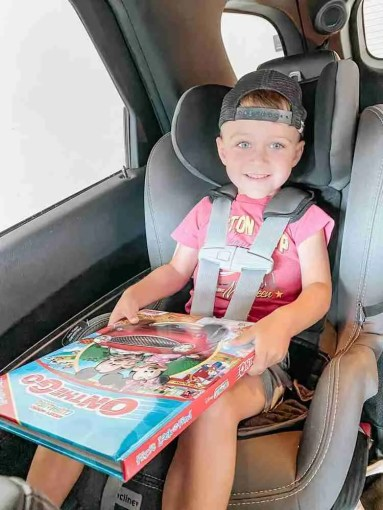 Toddler boy reading a book on a road trip