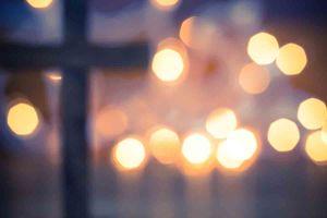 Das Anzünden einer Kerze, das Kreuz für Christus (Foto: enterlinedesign/ Shutterstock)