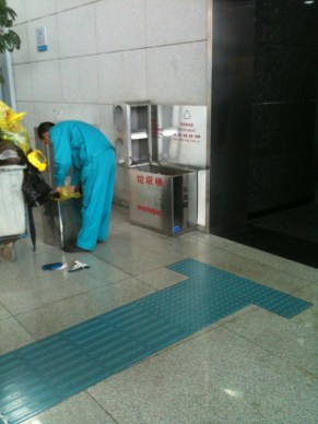 Qingdao Airport Maintenance Worker: completing his dirty deed. The trash and recycling are not supposed to mix!