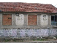 Four faded portraits of former politicians are on the outside walls of the community building.