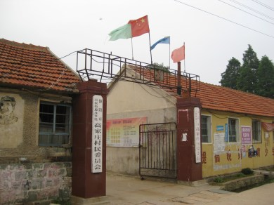 Gao Jia's Community Building: flags and portraits of famous Chinese politicians serve as decoration to an otherwise unremarkable building.