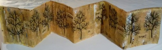 """Mary Housley. My version of the winter tree line.. A group that I meet with had a challenge of producing a piece of work with text in, so the words on this piece say """"he who plants a tree plants hope"""""""