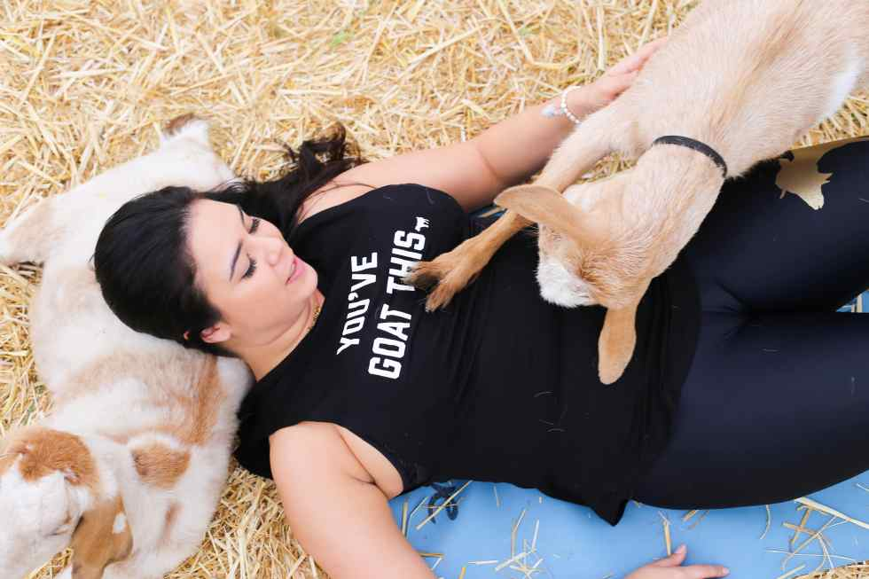 Woman doing yoga with goat