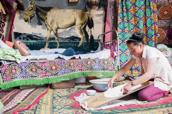 Aisholpan, campionessa mondiale di falconeria, nella gher prepara la cena mentre il padre riposa.