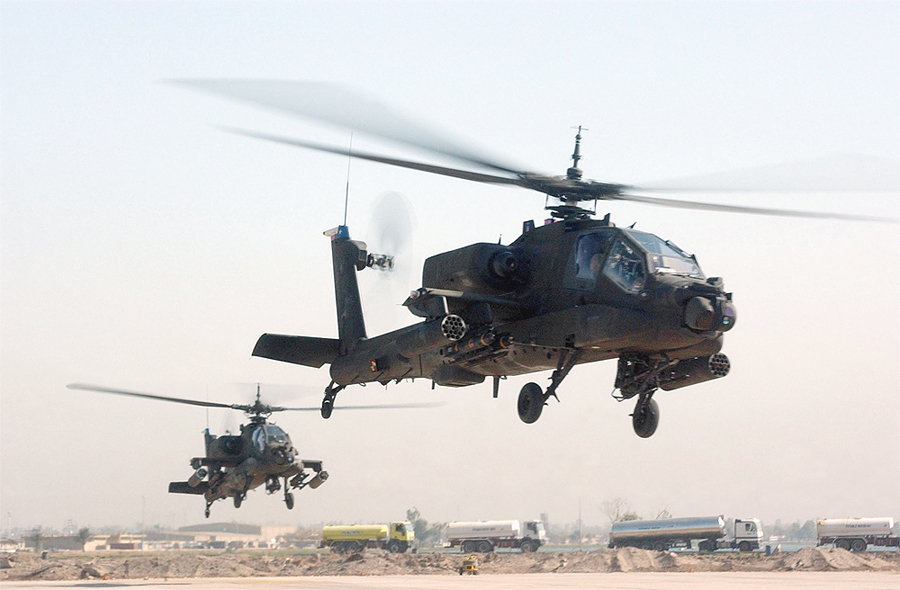 Two U.S. Army Apache helicopters take off from Camp Victory, BIAP, Baghdad Province, Iraq in 2008.