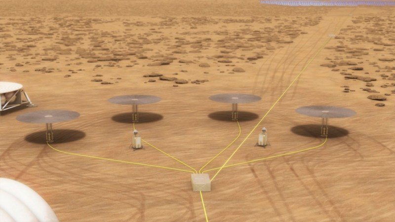 An artist's depiction of the Kilopower nuclear reactor, with a mushroom-like shape, working in concert with others on a reddish surface, presumably Mars.