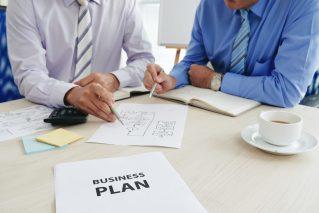 dois-homens-de-terno-avaliando-o-documento-com-titulo-business-plan-para-representar-a-preparaçao-para-a-compra-e-venda-de-empresas