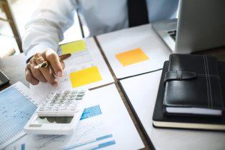 homem-diante-de-relatorios-e-calculadora-calculando-quanto-vale-sua-empresa-para-representar-os-custos-para-vender-uma-empresa