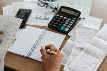 foto-de-pessoa-diante-de-um-caderno-e-sua-calculadora-para-ilustrar-a-elaboracao-de-uma-planilha-para-o-planejamento-financeiro-empresarial