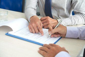 foto-de-duas-pessoas-assinando-um-contrato-que-contem-a-clausula-mac