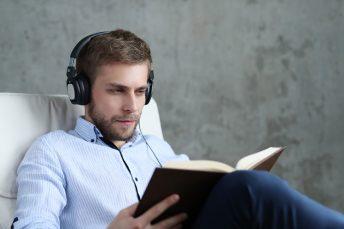 foto-de-homem-com-fone-de-ouvido-ouvindo-podcast-e-lendo-um-livro