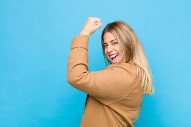 foto-de-mulher-fazendo-sinal-de-forca-em-fundo-azul-para-representar-empreendedorismo-feminino