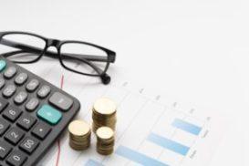 foto-de-moedas-e-calculadora-representando-o-custo-historico-para-calcular-o-valor-de-uma-marca
