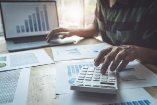 foto-de-pessoa-usando-calculadora-e-analisando-graficos-para-calcular-o-valor-da-empresa