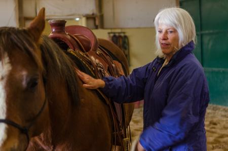 Lindy Wallace, president of the board overseeing the Colorado Health Insurance Cooperative, Inc., with her horse Joe.  Credit: JW Stephens/Colorado Public News