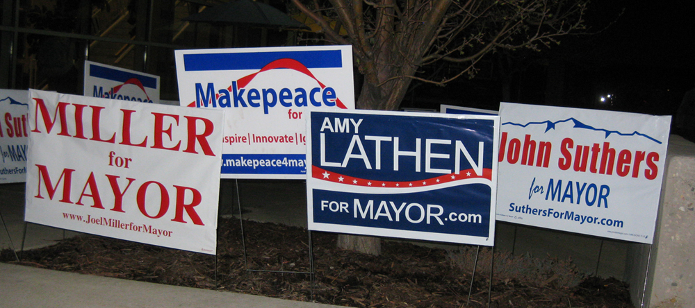 Campaign signs for the four candidates participating in a debate at UCCS.