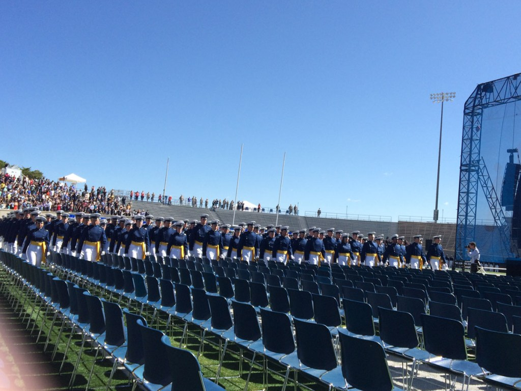 Graduating cadets file into rows of chairs at Falcon Stadium for commencement.