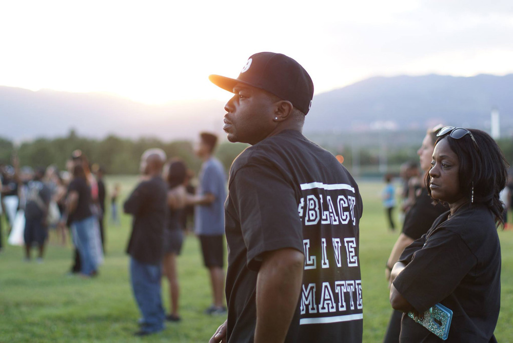 Attendees at Saturday's vigil in Memorial Park listen to speakers