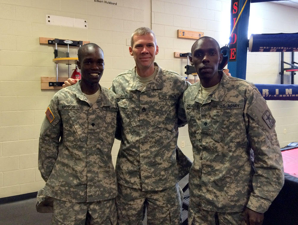 "2016 track and field Olympians, from left, Spc. Shadrack Kipchirchir, Staff Sgt. John Nunn and Spc. Paul Chelimo pose in Fort Carson's boxing training room, nicknamed ""The House of Pain."""