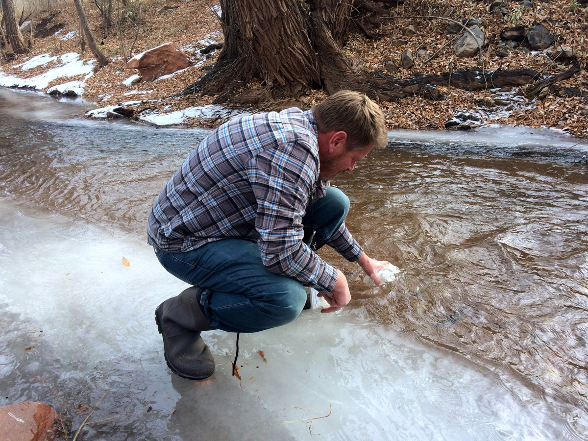 Colorado Springs Utilities environmental technician Corey Thiel collects chilly water samples for testing.