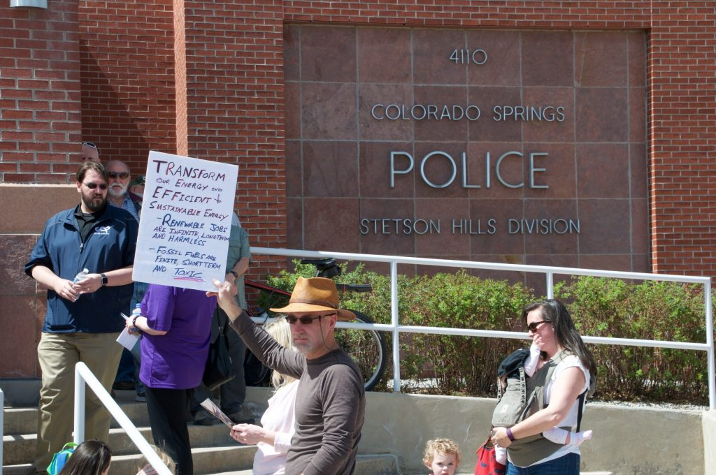 A protestor stands outside the Stetson Hills police substation in Colorado Springs. Dozens of people were turned away at the door due to lack of space inside the town hall venue.