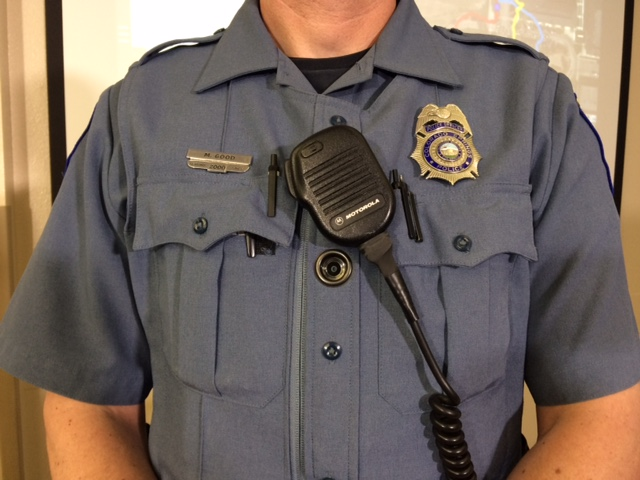 The department's body cameras are worn on a bullet proof vest. They peak through a hole in the police shirt.