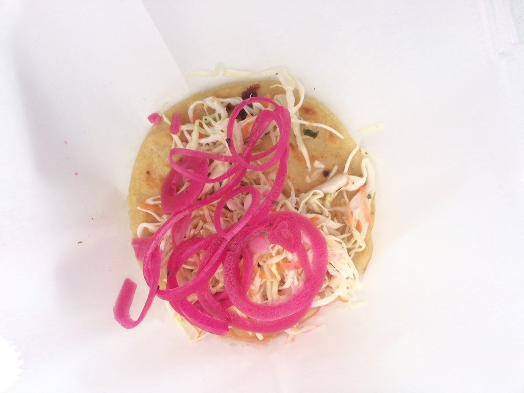 Pupusas are made with loroco and served with pickled onions.