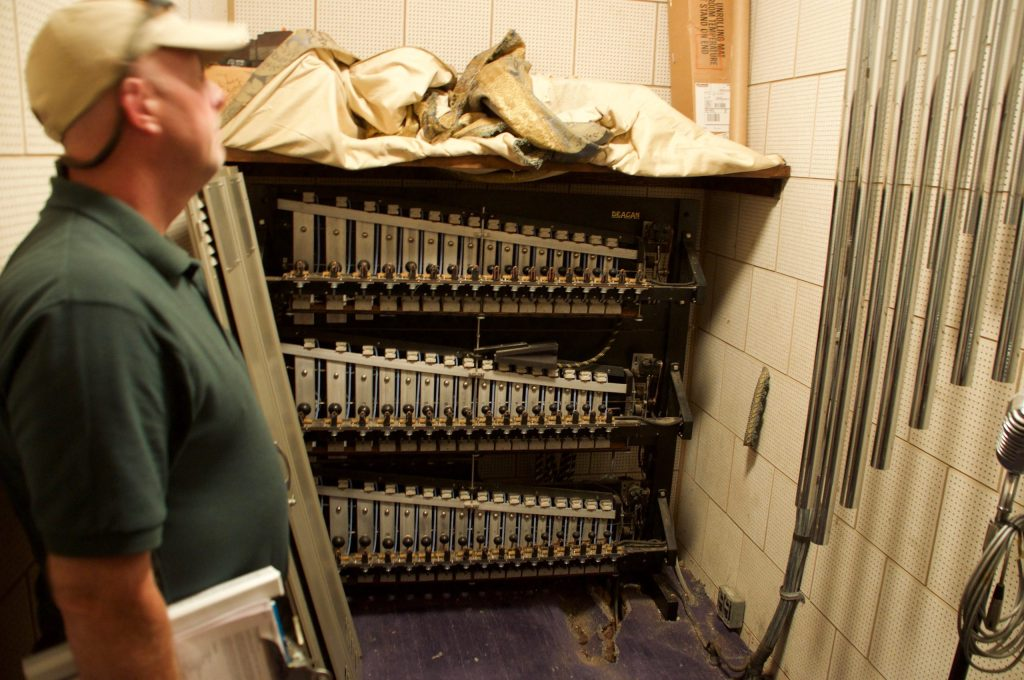 Will Rogers Shrine Curator Kevin Wynn with vintage chimes in the bowels of the Will Rogers Shrine.